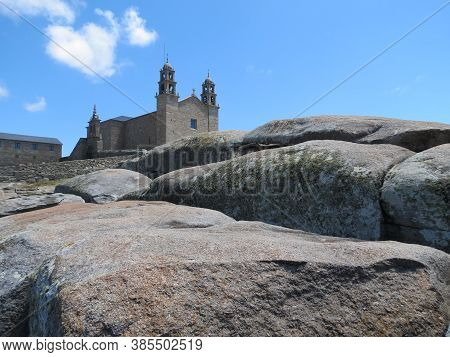 Church Virgen De La Barca Behind Huge Water Polished Ancient Sacral Stones On The Beach In Muxia, Sp