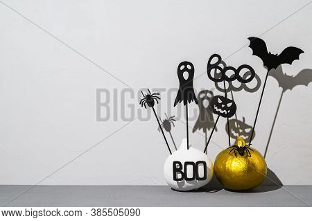 Halloween Home Decorations. Painted White And Gold Pumpkins With Scary Black Halloween Objects With