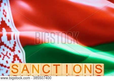 Sanctions. Wooden Blocks With The Inscription Sanctions On The Background Of The Flag Of Belarus