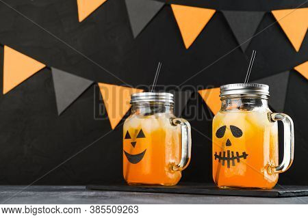 Halloween Pumpkin Iced Mocktails In Glass Jars Decorated With Scary Faces On A Dark Table. Diy Hallo