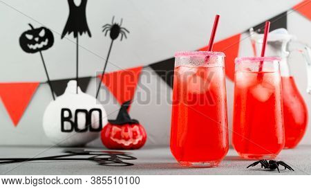 Iced Pumpkin Cocktails In Glasses Decorated With Scary Faces On A Gray Table. Diy Halloween Party De