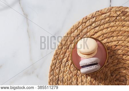 Macaron Cookie In A Pink Plate On Straw Woven Placemat. Marble Background