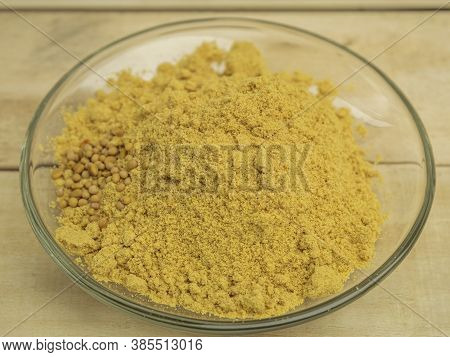 Seasoning Mustard Powder In A Glass Plate On A Wooden Background
