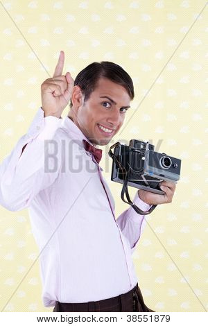 Man holding medium format camera pointing finger upward.