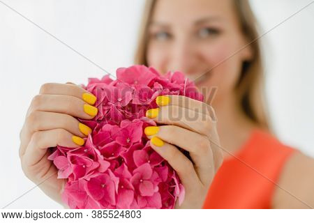 Women with manicured nails in yellow holding a flower in her hand