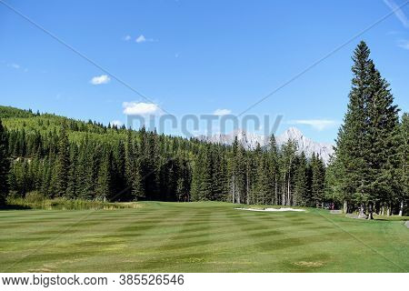 Gorgeous Par 4 On A Golf Course Surrounded By Forest And Big Mountains In The Background, On A Beaut