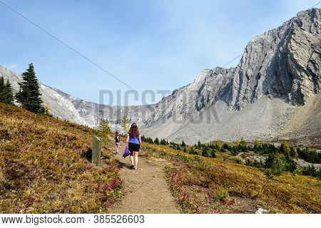 A Mother And Daugther Hiking A Beautiful Trail Above The Treeline With A Huge Mountain In The Backgr