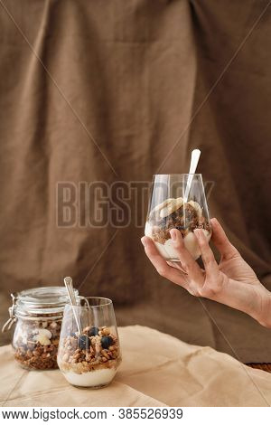 Hand Holding Delicious Layered Dessert In Glass Jar, Homemade Yogurt With Granola And Berries, Grano