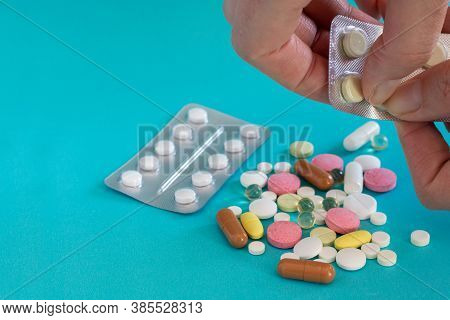 Get The Pills Out Of The Blister. Pill In Hand. Pills And Pills On A Blue Background. Medical Tablet