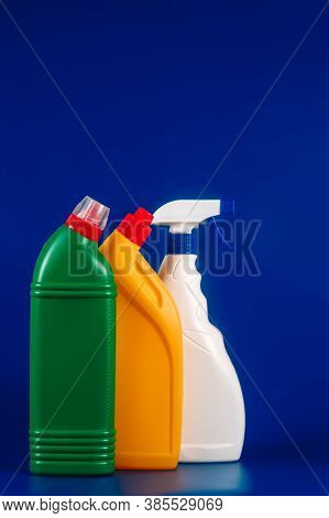 Different Color Bottles With Detergent On A Blue Background.