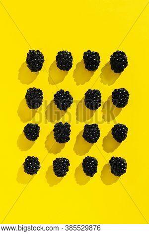 Blackberries Isolated On Illuminating Yellow Background. Trendy Flat Lay Pattern. Summer Juicy Black