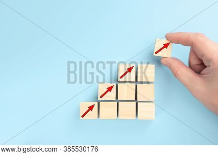 Concept Of Revenue Growth. Growth On Stacked Wooden Cubes On Blue Background. Financial Or Business