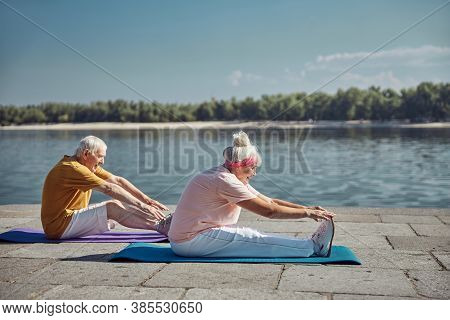 Two Senior Beginner Yogis Performing A Stretching Exercise