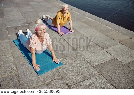 Smiling Pensioners Performing An Upward-facing Dog Exercise
