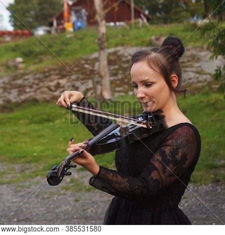 Beautiful Young Woman In Black Dress Playing Violin In An Outdoor Setting