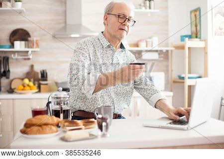 Retired Man Entering Pin Number While Shopping Online On The Internet. Pensioner Paying Online Using