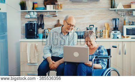 Disabled Senior Woman In Wheelchair Waving During A Video Conference Sitting Next To Husband. Paraly