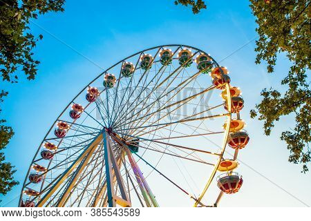 Ferries Wheel At Amusement Park Against Blue Sky And Tree Leaves.