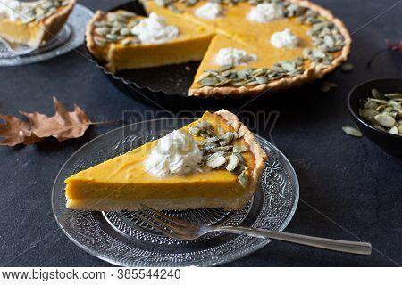 Slice Of Fresh Homemade Pumpkin Pie On Black Table.
