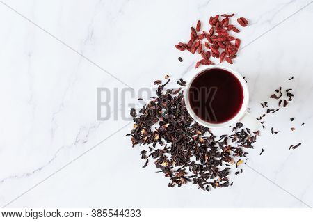 Red Hibiscus Tea  In Glass Mug And Goji Berries Top View On White Marble Background. Healthy Food, D