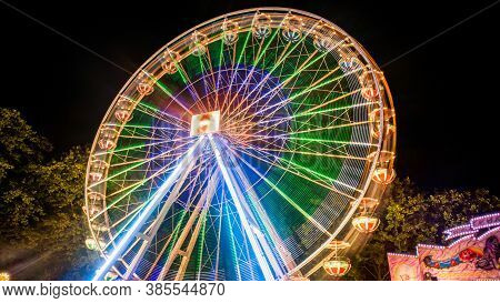 Ferries Wheel Rotating At Night With Lights At Amusement Park. Long Exposure Light.