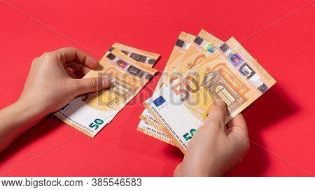 The Man Considers The Money Of The Banknote 50 Euros On A Red Background. Credit, Money Account, Sav