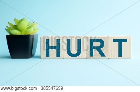 Hurt. Written On A Wooden Block. Text Hurt On Blue Background For Your Design, Coronavirus Concept T