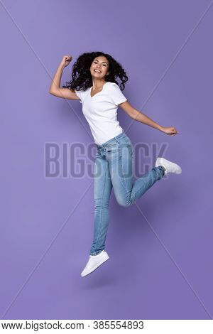 Happy Mexican Lady Jumping Posing In Mid-air Over Purple Background In Studio, Smiling Looking At Ca