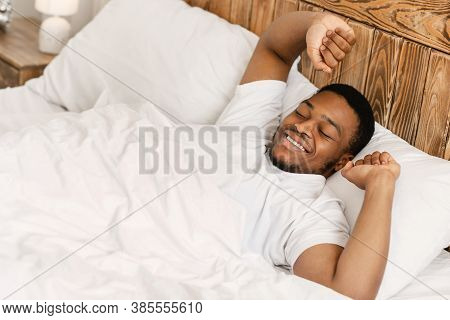 Happy Rested Wellslept Black Man Waking Up In The Morning Stretching Hands Lying In Comfortable Bed