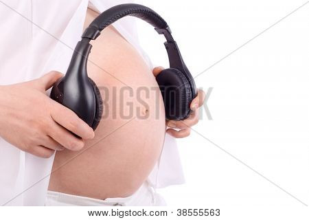 Hands of pregnant woman in white holding black headphones close to belly isolated on white background.