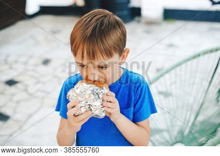 Hungry Boy Eating A Burger At Outdoors Cafe. Cute Child Eating Fast Food. Childhood, Unhealthy Food