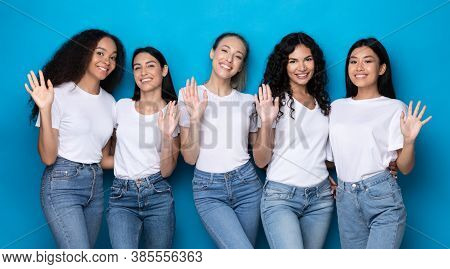 Hello Greeting. Five Multiethnic Women Waving Hand Smiling To Camera Posing On Blue Background. Chee