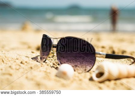 Sunglasses Lying On A Tropical Sandy Beach With Seashells And Stones. Sunglasses On The Beach. Nice