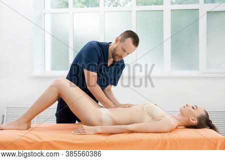 Positive Male Osteopath Treating Belly Of Patient