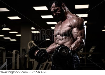 Strong Young Bearded Male Lifting Heavy Weight Dumbbells Training His Biceps Muscles In Dark Gym Dur