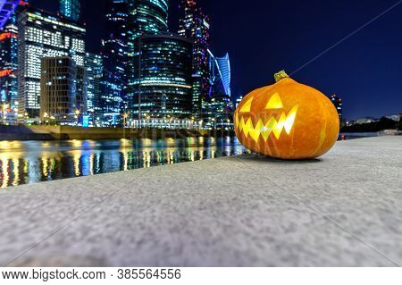 Halloween Pumpkin On The Background Of Moscow City Skyscrapers At Night. Multi-story Buildings And B