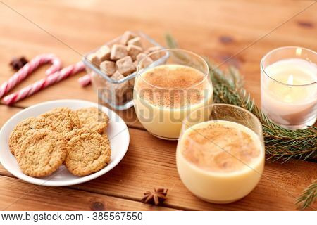 christmas and seasonal drinks concept - glasses of eggnog with oatmeal cookies, candy canes, sugar, fir tree branches and candle burning on wooden background