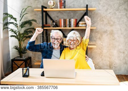 Overjoyed Mature Grey-haired Husband And Wife Looks On Laptop Indoor. Excited Senior Couple Rais Han