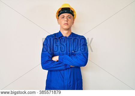 Young hispanic boy wearing worker uniform and hardhat skeptic and nervous, disapproving expression on face with crossed arms. negative person.