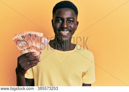 Young african american man holding south african rand banknotes looking positive and happy standing and smiling with a confident smile showing teeth