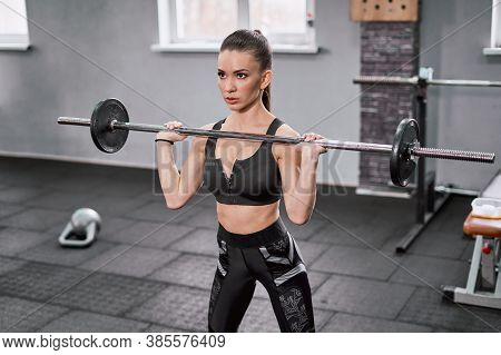 Sultry Brunette Doing A Barbell Workout In The Gym