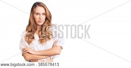 Young caucasian woman with blond hair wearing elegant summer tshirt skeptic and nervous, disapproving expression on face with crossed arms. negative person.
