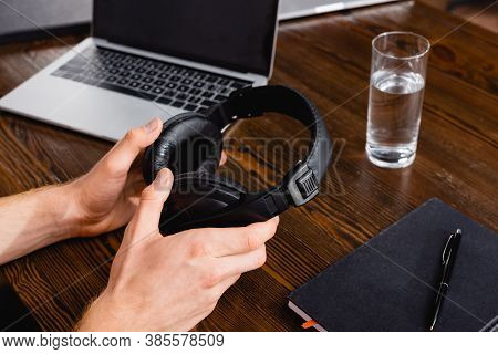 Partial View Of Freelancer Holding Wireless Headphones Near Laptop, Glass Of Water And Notebook With