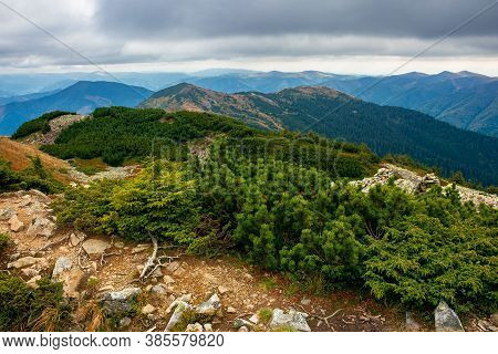 View From The Top Of A Mountain. Cloudy Autumn Scenery. Mountain Range Behind The Valley In The Dist