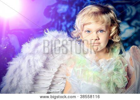 Beautiful little angel girl over Christmas background.
