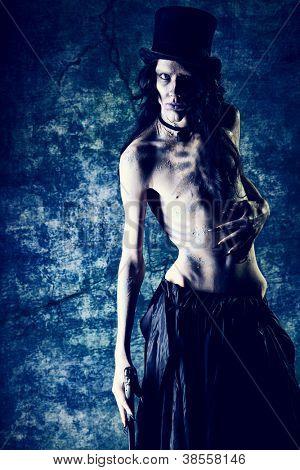 Gloomy vampire standing at the night background. Halloween.
