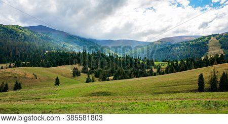 Autumnal Countryside Landscape. Beautiful Mountain Scenery On A Cloudy Day. Green Fields Rolling Thr