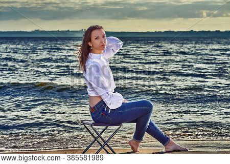 A Young Brunette Woman In A White Blouse And Blue Jeans Sits And Rests On The Sandy Seashore. Sunny