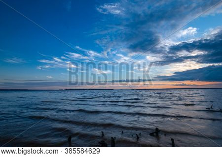 Blue Tranquil Minimalist Landscape With Lake With Wavy Water Surface With Horizon Under Dramatic Clo