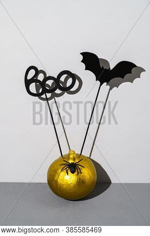 Halloween Decorations. Painted Golden Pumpkin With Scary Black Halloween Objects With Shadows On A G